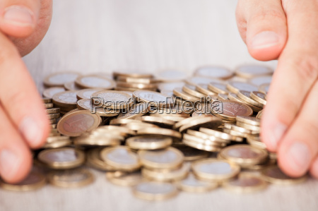 businessmans hands collecting euro coins