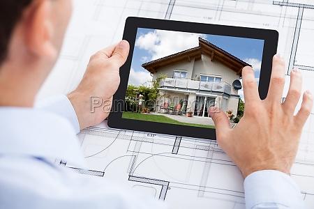 architect analyzing house on digital tablet