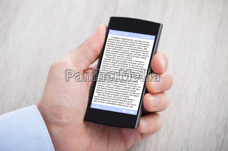businessmans hand displaying ebook on smartphone