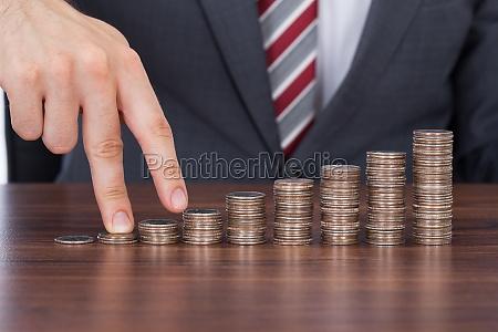 businessmans fingers walking up stack of