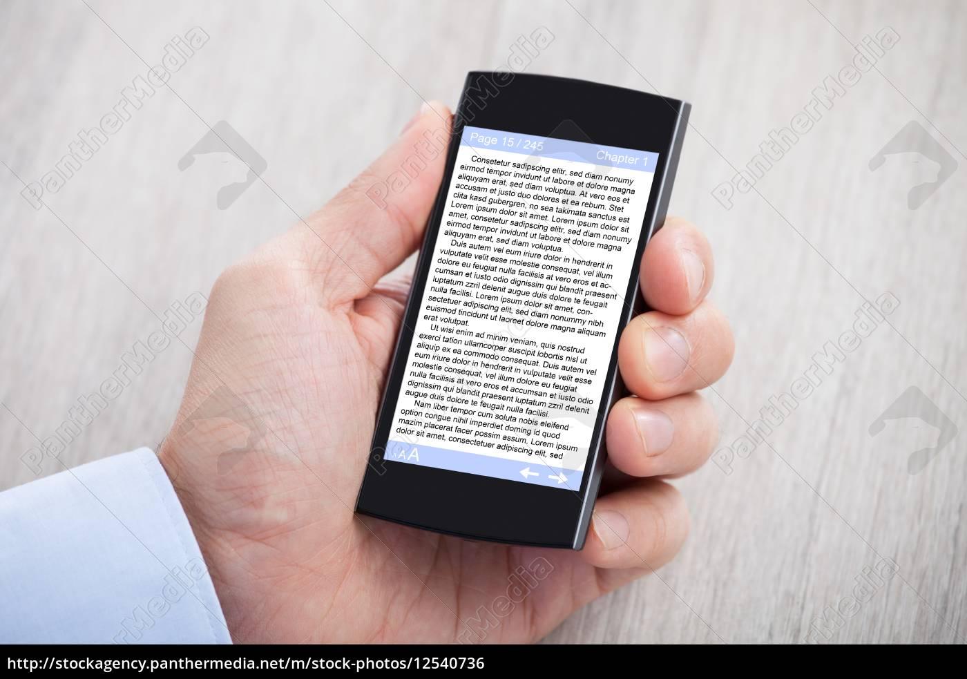 businessman's, hand, displaying, ebook, on, smartphone - 12540736