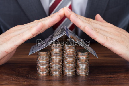 businessman sheltering coins and banknote in