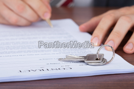 man signing contract with keys on
