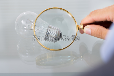 businessman inspecting lightbulb