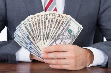 businessman, holding, fanned, banknotes - 12541086