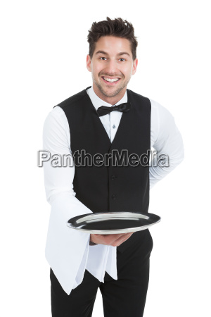 smiling young waiter holding empty serving
