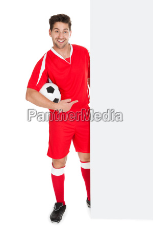 soccer player pointing at billboard