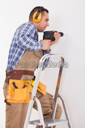 repairman drilling hole in wall