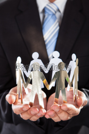 businessman holding metal team in cupped
