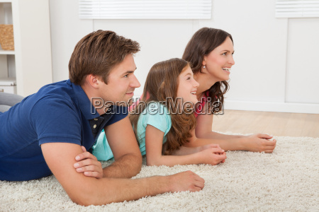 happy family lying on rug at