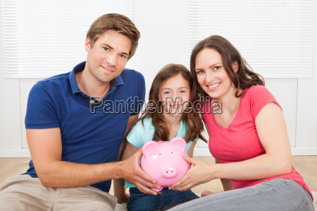 happy family holding piggy bank at