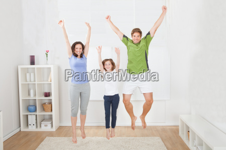 excited family in sportswear jumping at