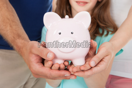 family holding piggy bank