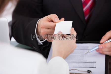 businessman, giving, visiting, card, to, colleague - 12543820