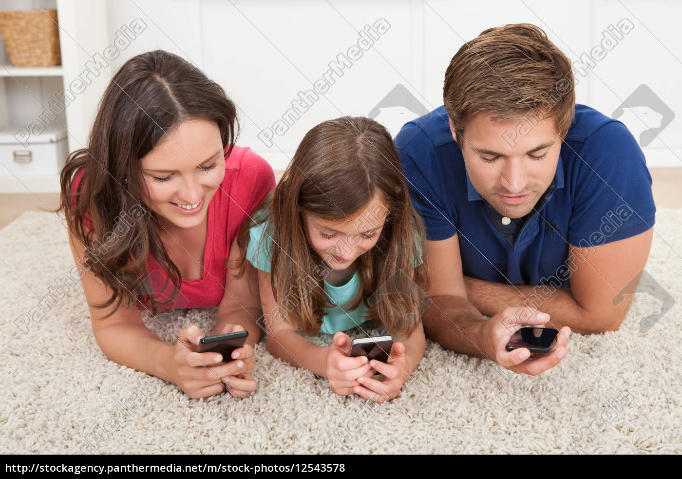 family, using, smart, phones, at, home - 12543578