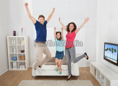 portrait, of, excited, family, jumping, at - 12543520