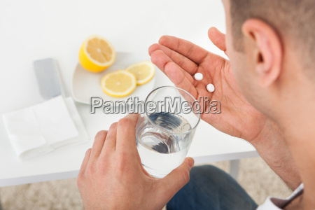 sick, man, taking, tablets, with, glass - 12543344
