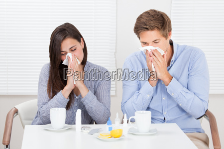 couple suffering from cold at table