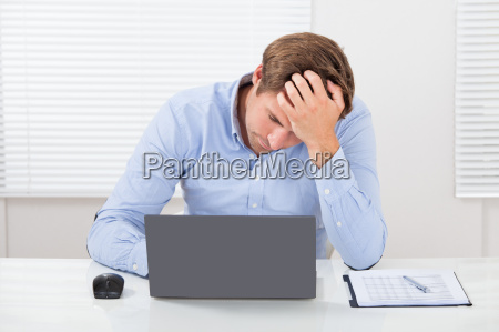stressed, businessman, using, laptop, in, office - 12544388