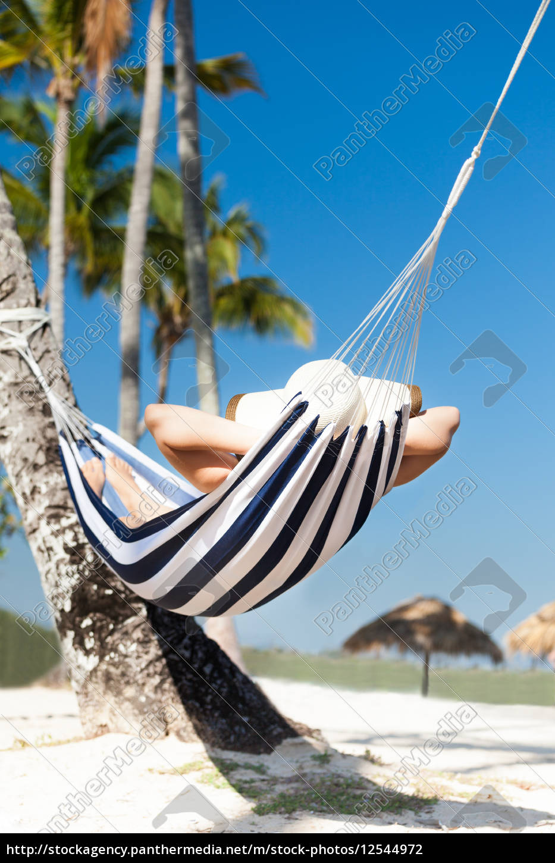 woman, in, hammock, at, beach - 12544972
