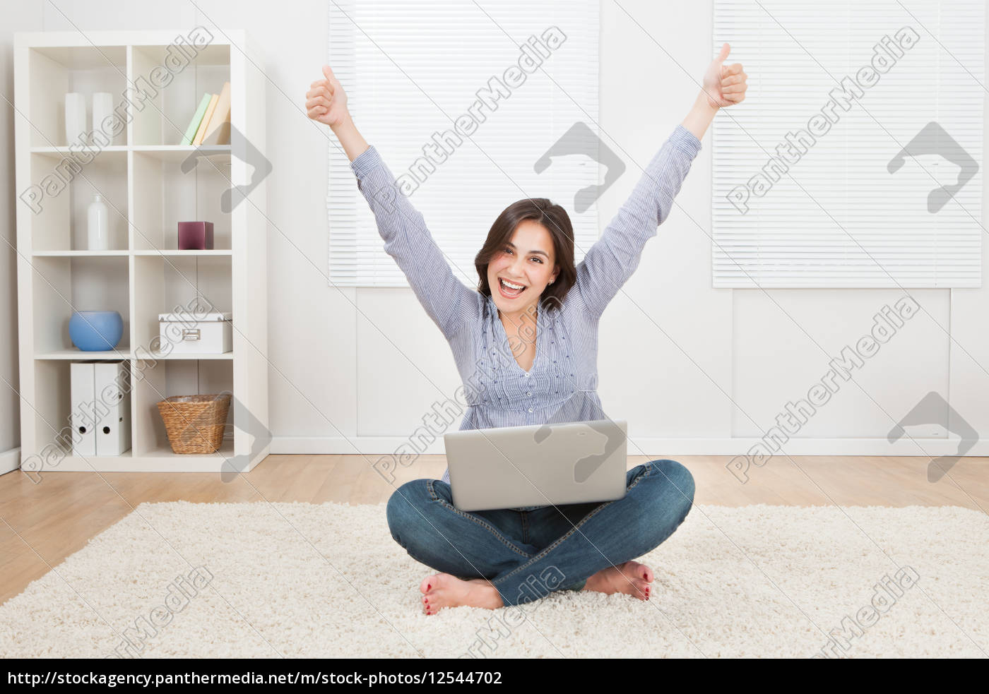 woman, raising, arms, while, using, laptop - 12544702