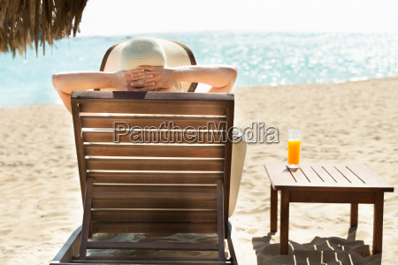 woman relaxing on deck chair at
