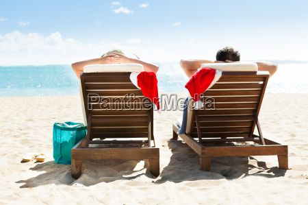 couple, with, santa, hats, relaxing, on - 12545952