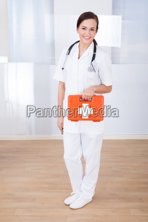 happy female doctor holding first aid