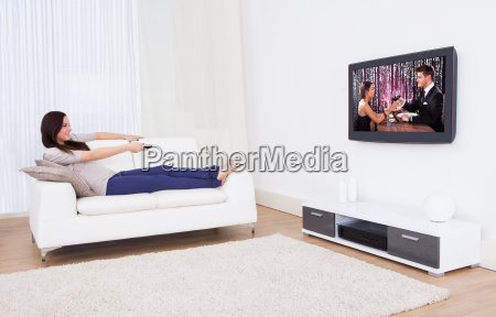woman watching tv while relaxing on