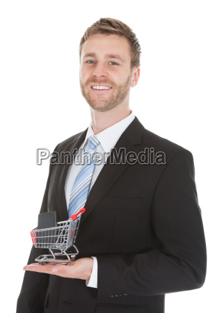 businessman holding shopping cart model with