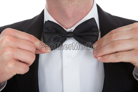midsection of waiter adjusting bowtie