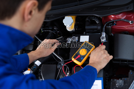 mechanic testing car battery