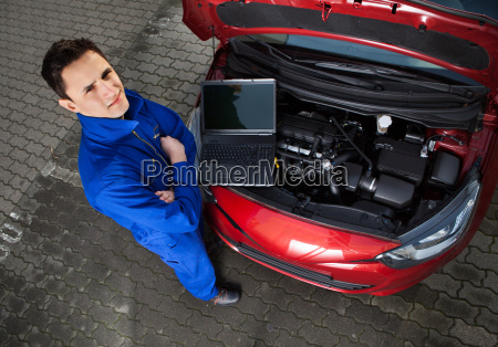 mechanic with arms crossed standing by