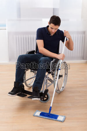 handicapped man mopping floor while sitting