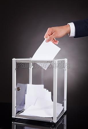 businessman inserting ballot in box on