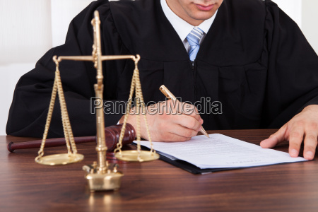 judge signing document at table in