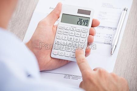 businessman calculating invoice at desk