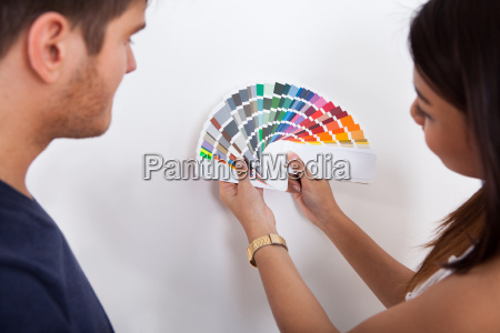 couple choosing color for wall at