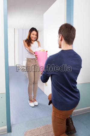 man kneeling while giving bouquet to