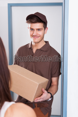 delivery, man, giving, courier, to, woman - 12553796