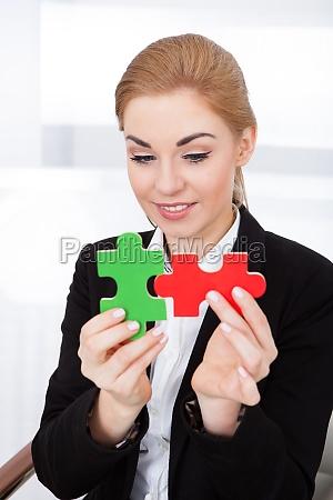 businesswoman holding jigsaw puzzle