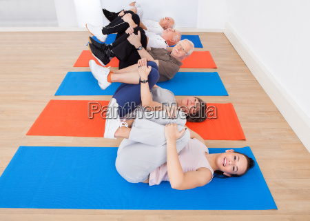 people exercising on mats at gym