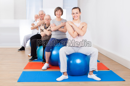 trainer and senior customers sitting on