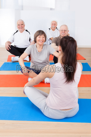 trainer training customers in yoga class