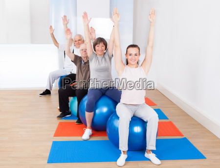 trainer and senior customers stretching on