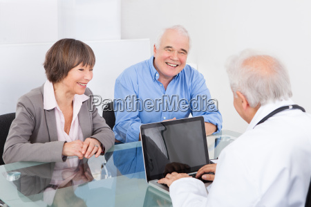 happy couple discussing with male doctor