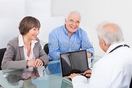 pareja feliz que discuten con doctor