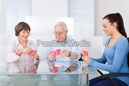 caretaker playing cards with senior couple