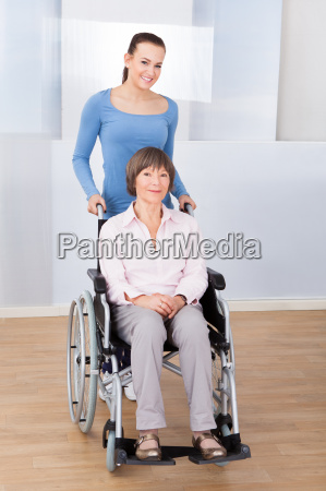 caregiver with disabled senior woman in