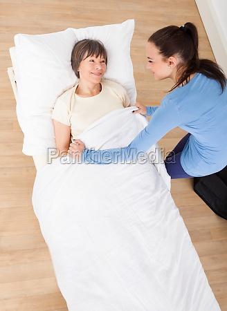 caretaker covering senior woman with blanket